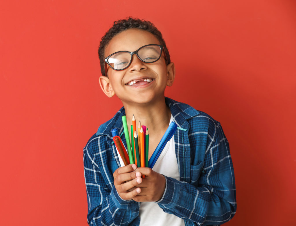 Child smiling with crayons